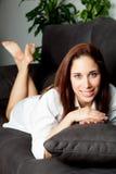Chica joven que se relaja en el sofá en casa Foto de archivo