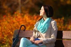 Chica joven que se relaja en parque otoñal. Concepto de la forma de vida de la caída. Foto de archivo libre de regalías
