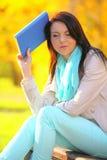 Chica joven que se relaja en parque otoñal. Concepto de la forma de vida de la caída. Imágenes de archivo libres de regalías