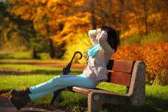 Chica joven que se relaja en parque otoñal. Concepto de la forma de vida de la caída. Imagen de archivo libre de regalías