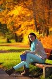 Chica joven que se relaja en parque otoñal. Concepto de la forma de vida de la caída. Fotografía de archivo
