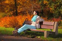 Chica joven que se relaja en parque otoñal. Concepto de la forma de vida de la caída. Foto de archivo