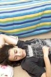 Chica joven que se relaja en suelo Imagen de archivo libre de regalías