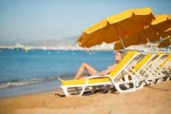 Chica joven que se relaja en una silla de playa cerca del mar Foto de archivo libre de regalías