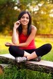 Chica joven que se sienta al aire libre en banco Foto de archivo libre de regalías
