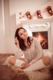 Chica joven que se sienta al lado de la chimenea Fotografía de archivo