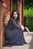 Chica joven que se sienta cerca de casa de madera en la naturaleza Foto de archivo