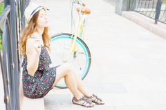 Chica joven que se sienta cerca de la bici del vintage en el parque Fotografía de archivo libre de regalías