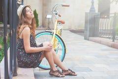 Chica joven que se sienta cerca de la bici del vintage en el parque Foto de archivo