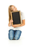 Chica joven que se sienta con la pizarra vacía sobre el fondo blanco Foto de archivo libre de regalías