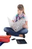 Chica joven que se sienta con PC y el teléfono de la tablilla Imágenes de archivo libres de regalías