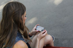Chica joven que se sienta con un teléfono en su mano Fotos de archivo