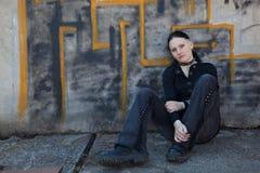 Chica joven que se sienta delante de la pared de la pintada Imágenes de archivo libres de regalías