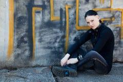 Chica joven que se sienta delante de la pared de la pintada Imagen de archivo libre de regalías