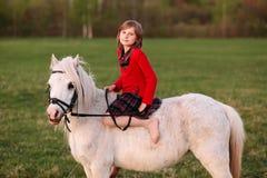 Chica joven que se sienta descalzo en un caballo blanco Foto de archivo libre de regalías
