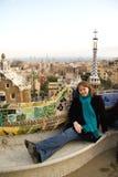 Chica joven que se sienta en banco del mosaico en el parque Guell Fotos de archivo