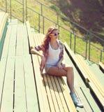 Chica joven que se sienta en banco en parque de la ciudad en verano soleado fotos de archivo libres de regalías