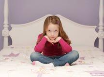 Chica joven que se sienta en cama Imágenes de archivo libres de regalías