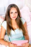 Chica joven que se sienta en cama Foto de archivo