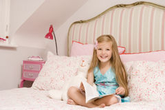 Chica joven que se sienta en cama con la sonrisa del libro Imágenes de archivo libres de regalías