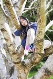 Chica joven que se sienta en el árbol de abedul, sonriendo Imágenes de archivo libres de regalías