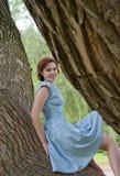 Chica joven que se sienta en el árbol grande Imagen de archivo libre de regalías