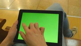 Chica joven que se sienta en el banco en alameda de compras y el funcionamiento con la tableta Manos femeninas usando la PC de la almacen de video