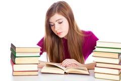 Chica joven que se sienta en el escritorio Imágenes de archivo libres de regalías