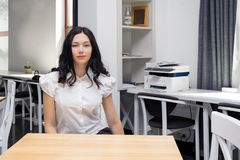 Chica joven que se sienta en el escritorio Aliste para el trabajo, estudio Imágenes de archivo libres de regalías