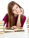 Chica joven que se sienta en el escritorio y el libro de lectura. Foto de archivo libre de regalías