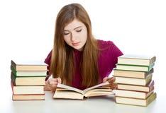 Chica joven que se sienta en el escritorio y el libro de lectura Foto de archivo