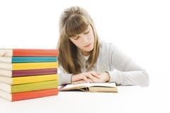 Chica joven que se sienta en el escritorio y el libro de lectura. Imagenes de archivo