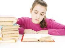 Chica joven que se sienta en el escritorio y el libro de lectura Imagenes de archivo