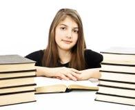 Chica joven que se sienta en el escritorio y el libro de lectura Fotografía de archivo