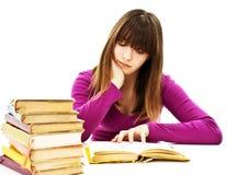 Chica joven que se sienta en el escritorio y el libro de lectura Imagen de archivo