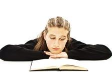 Chica joven que se sienta en el escritorio y el libro de lectura Fotos de archivo libres de regalías