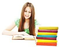 Chica joven que se sienta en el escritorio y el libro de lectura Fotografía de archivo libre de regalías