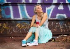 Chica joven que se sienta en el monopatín Fotografía de archivo libre de regalías