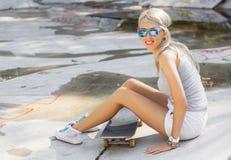 Chica joven que se sienta en el monopatín en skatepark Foto de archivo
