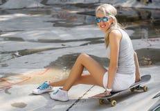 Chica joven que se sienta en el monopatín en skatepark Fotos de archivo