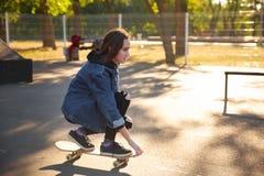Chica joven que se sienta en el monopatín skateboarding Al aire libre, forma de vida Fotos de archivo libres de regalías
