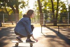 Chica joven que se sienta en el monopatín skateboarding Al aire libre, forma de vida Fotografía de archivo