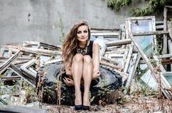 Chica joven que se sienta en el neumático del camión Fotografía de archivo libre de regalías