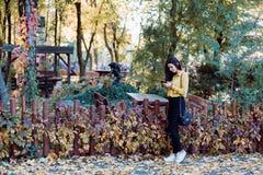 Chica joven que se sienta en el parque que comprueba su teléfono Imagen de archivo libre de regalías