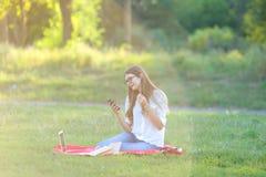 Chica joven que se sienta en el parque, sonriendo y trabajando en su ordenador portátil, escuchando la música Foto de archivo libre de regalías