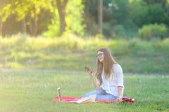 Chica joven que se sienta en el parque, sonriendo y trabajando en su ordenador portátil, escuchando la música Fotografía de archivo libre de regalías