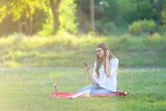 Chica joven que se sienta en el parque, sonriendo y trabajando en su ordenador portátil, escuchando la música Imagen de archivo libre de regalías