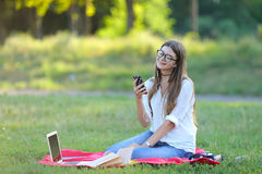 Chica joven que se sienta en el parque, sonriendo y trabajando en su ordenador portátil, escuchando la música Fotos de archivo libres de regalías