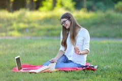 Chica joven que se sienta en el parque, sonriendo y trabajando en su ordenador portátil, escuchando la música Fotos de archivo