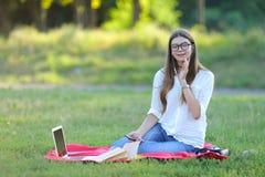Chica joven que se sienta en el parque, sonriendo y trabajando en su ordenador portátil, escuchando la música Imágenes de archivo libres de regalías